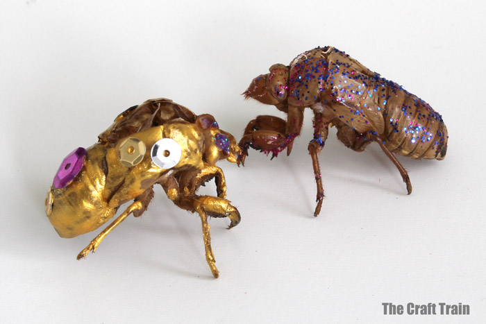two cicada shells decorated with paint and glitter