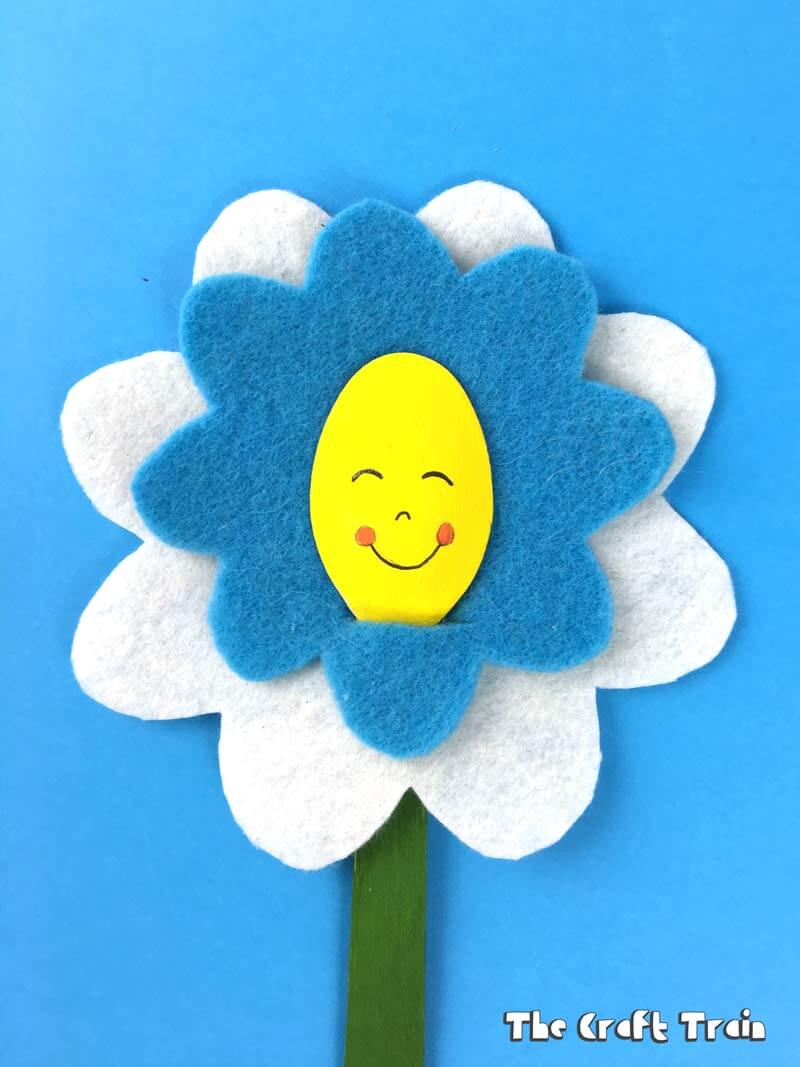Happy flower craft idea for kids, blue and white felt flower on blue background #flowercraft #kidscrafts #feltcrafts