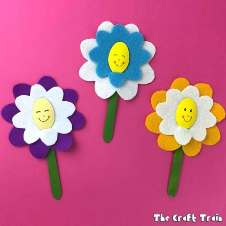 Happy flowers from felt and wooden teaspoons on pink background #flowercrafts #kidscrafts #feltcrafts #Spring #Springcrafts