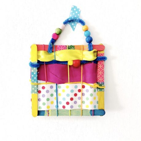 Simple weaving project for kids. Create colourful works of art using craft sticks and ribbon scraps #finemotor #weaving #kidscrafts