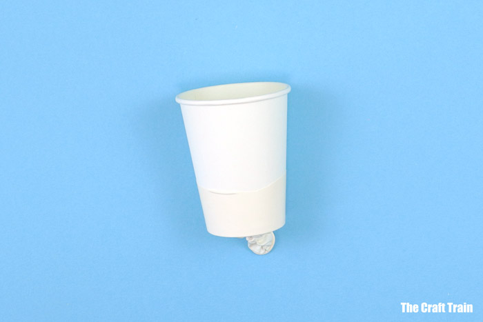 stretch balloon over base of paper cup
