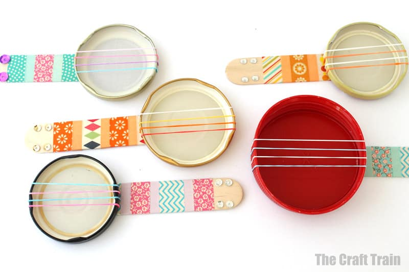 Mini banjo craft for kids made from a repurposed jar lid and loom bands