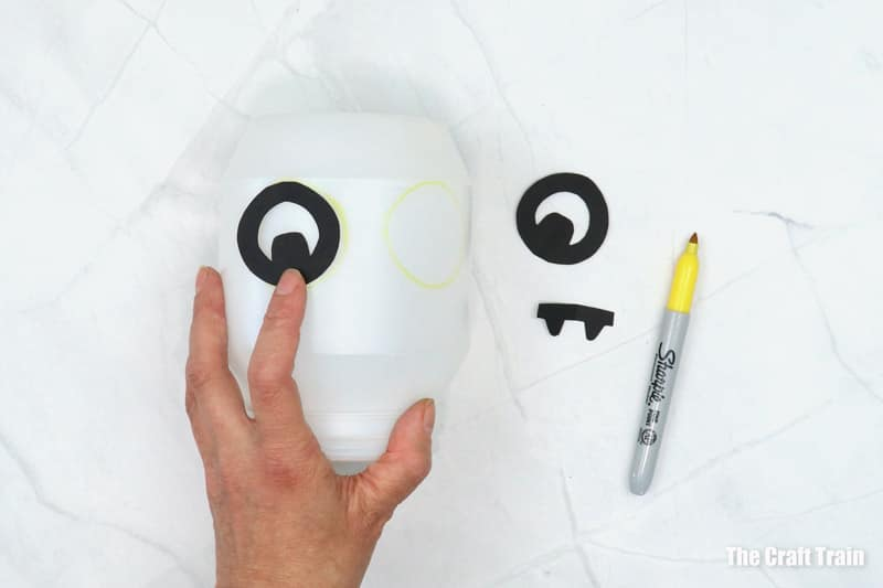 Monster features being traced onto plastic container